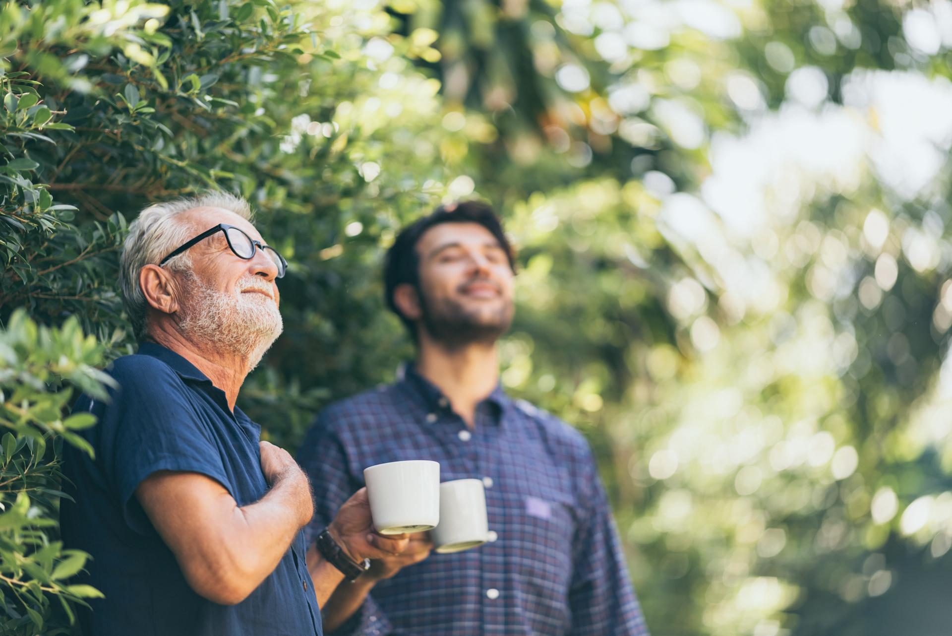 Vater und Sohn trinken gemütlich Kaffee im Garten